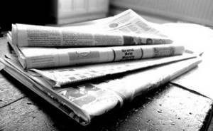 newspapers stack on table black and white